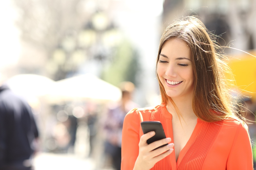 A lady holding a phone smiling