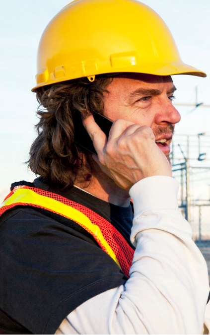 Construction worker hold mobile phone to ear