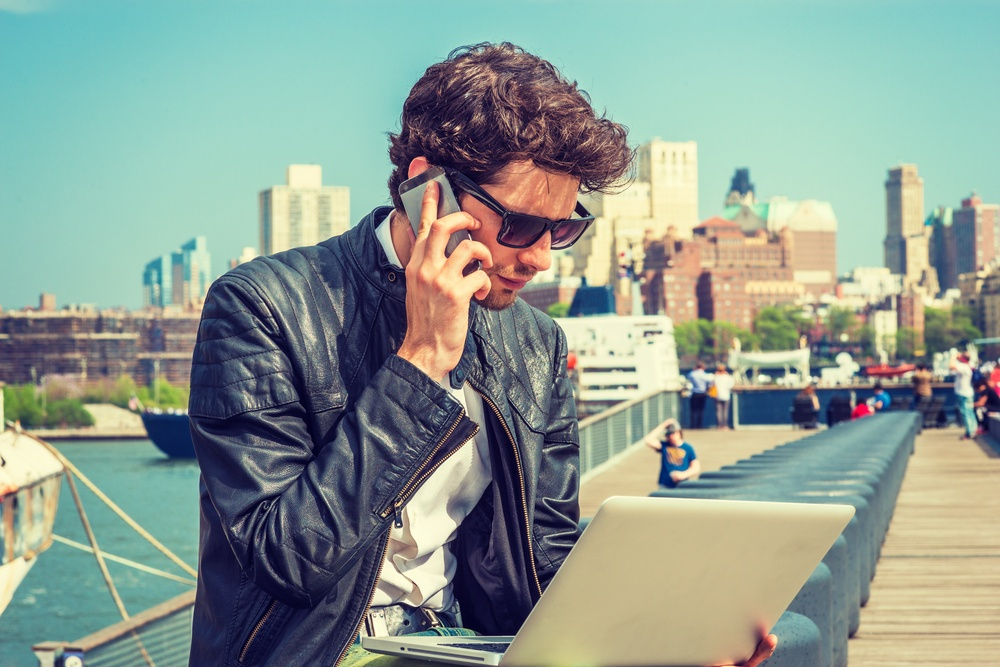 Mobile worker on the phone and holding a laptop.jpg
